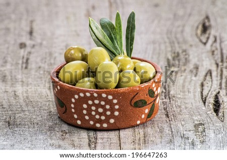 Green olives in great wooden background - stock photo
