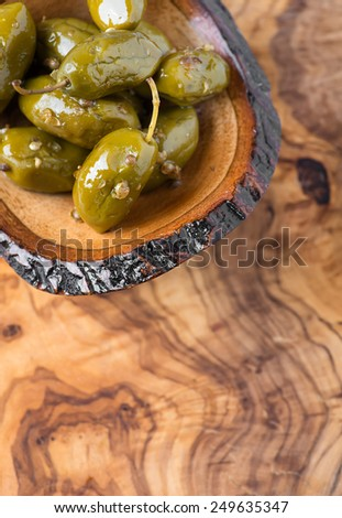 Green olives marinated with coriander in small wooden bowl over olive wood board, selective focus, copy space, top view - stock photo