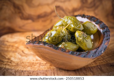 Green olives marinated with coriander in small wooden bowl over olive wood board, selective focus - stock photo