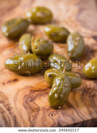 Green olives marinated with coriander over olive wood board, selective focus - stock photo