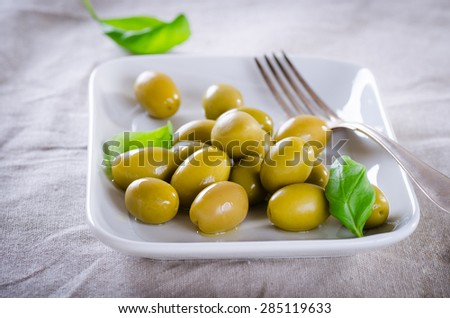Green olives on a white plate - stock photo