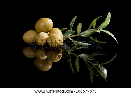 Green olives with olive branch isolated on black background. Culinary traditional appetizer. - stock photo