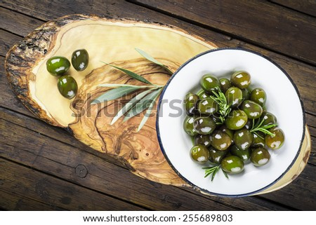 Green olives with rosemary and olive oil on a vintage plate on the table of the kitchen - stock photo
