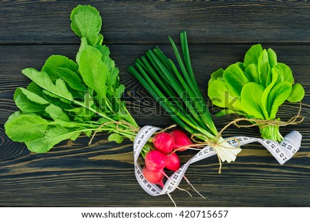 Green onions , radishes , lettuce leaves on a dark wooden table . Fitness, Healthy Eating - stock photo