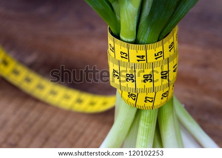 Green onions with yellow measurement tape on rustic wooden background; weight loss and diet concept - stock photo