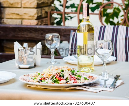 Green Organic Caesar Salad with Cheese and Croutons with white wine at the terrace restaurant - stock photo