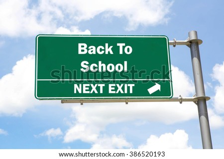 Green overhead road sign with a Back To School Next Exit concept against a partly cloudy sky background.  - stock photo