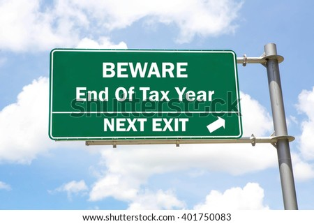 Green overhead road sign with a Beware of the End Of The Tax Year Next Exit concept against a partly cloudy sky background. - stock photo