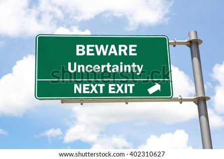 Green overhead road sign with a Beware Uncertainty Next Exit concept against a partly cloudy sky background. - stock photo