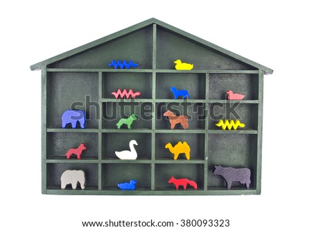 Green painted wooden shelf with a roof filled with various wooden animal toy figurines isolated on white - stock photo