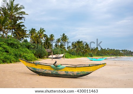 Green palms and fishermen's boats at empty beach in Weligama, Sri Lanka - stock photo