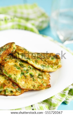 Green pancakes with zucchini and herbs - stock photo
