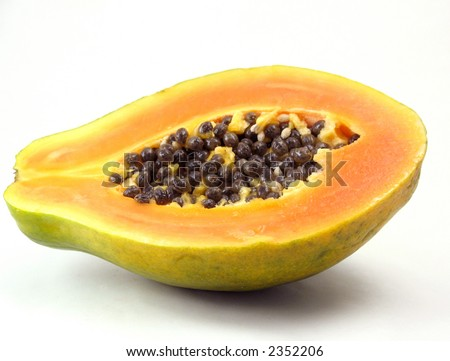 Green papaya with orange and yellow flesh and black seeds, cut in half on white background. - stock photo