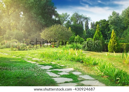 Green park with walkway and bench under the tree. Beautiful place for leisurely walk. - stock photo
