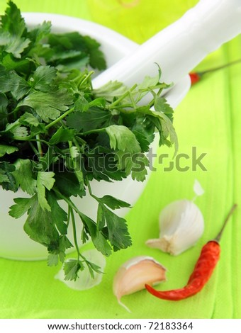 green parsley in a mortar with garlic and pepper on a green napkin - stock photo