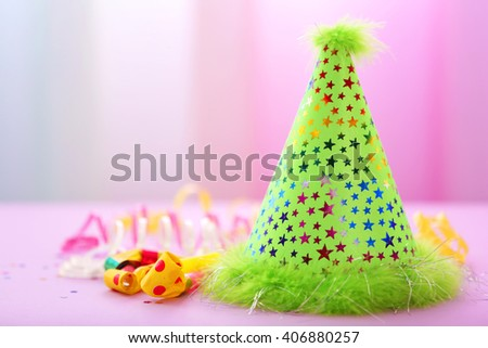 Green party hat on bright background - stock photo
