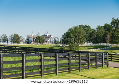 Green pastures of horse farms with black wooden fence on foreground. Country summer landscape. - stock photo