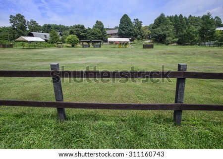 Green pastures of horse farms with wooden fence - stock photo