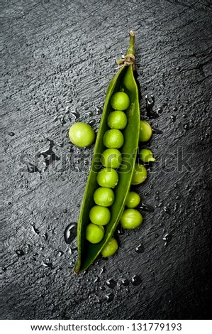Green pea in the pod on dark slate - stock photo