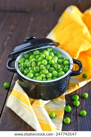 green peas in bowl and on a table - stock photo