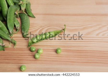 green peas in pods freshly picked on wood. Some green peas. Fresh green peas. green pods with peas as background. - stock photo