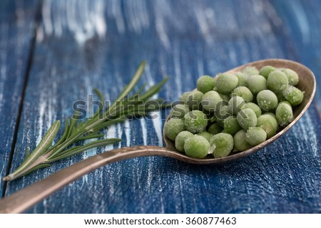 Green peas in silver spoon with a sprig of rosemary on blue wooden background - stock photo