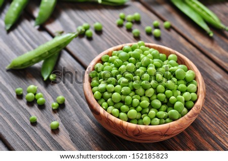 Green peas in wooden bowl on wooden background - stock photo
