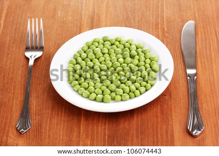 Green peas on plate on wooden background - stock photo
