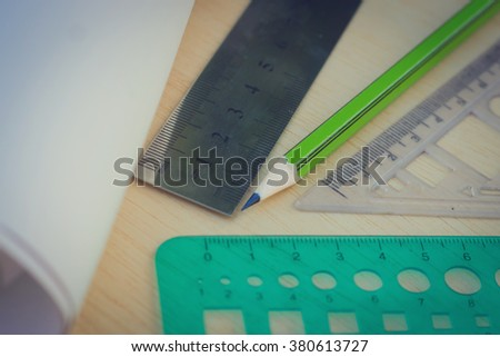 green pencil, steel ruler, triangle ruler, Geometry ruler and scroll on wood texture in vintage style - stock photo