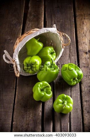 Green peppers group in rustic wicker basket on old rustic wooden table in studio - stock photo