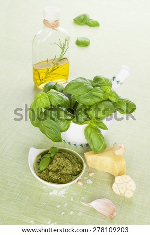 Green pesto background. Extra virgin olive oil, green pesto, parmigiano and fresh basil herbs on bright green background. Organic mediterranean eating.  - stock photo