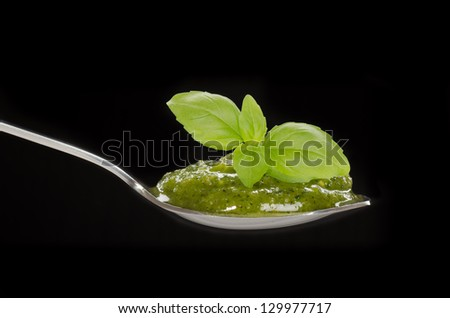 Green pesto in a spoon with basil leaf - stock photo