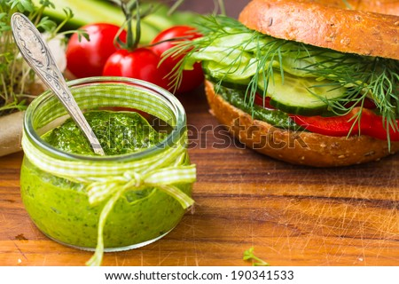 Green pesto in little jar. Vegan bagel and raw vegetables in the background. Selective focus on pesto.  - stock photo