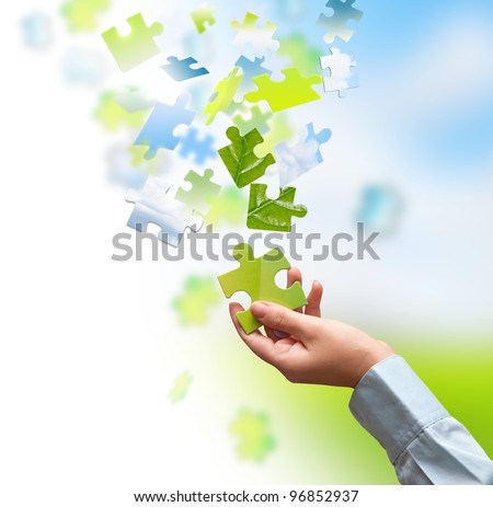 Green piece of a puzzle in hand - stock photo
