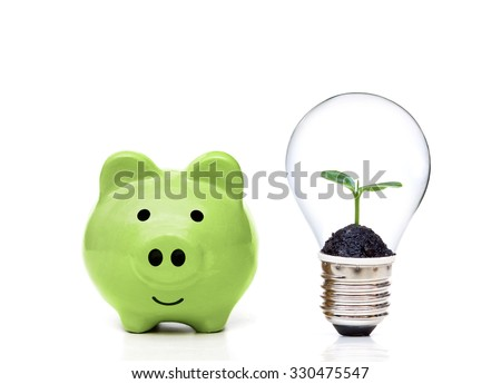 Green piggy bank and a lightbulb with a tree inside - Living Green and Saving Energy  - stock photo