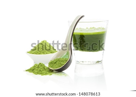 Green pills, green powder, green drink and wheat grass blades isolated on white background. Chlorella, spirulina, wheat grass and barley grass. Healthy natural herbal medicine, healthy lifestyle. - stock photo