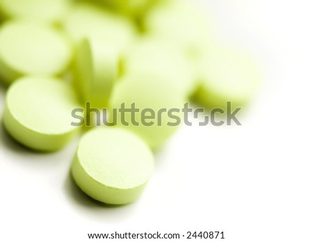 Green pills over white macro shot - stock photo