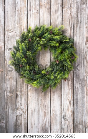 Green Pine Christmas wreath on old wooden door - stock photo