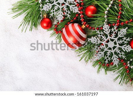 Green pine tree branch with  Christmas balls on snow background - stock photo