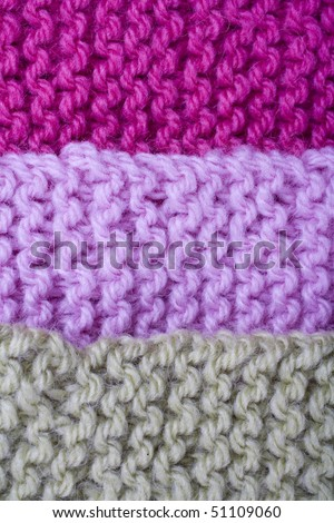 Green, pink and crimson knit lined up. - stock photo