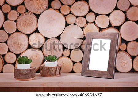 Green plants in white pot with frame on wooden background - stock photo
