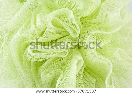 Green plastic bath sponge on white background - stock photo