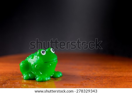 Green plastic frog enjoys a puddle of water - stock photo