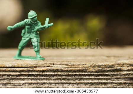 Green plastic toy soldier army unit throwing a grenade on top of an old weathered railway sleeper. Selective focus and wooden textured background  - stock photo