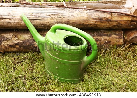 green plastic water can horizontal photo on lawn summer background - stock photo