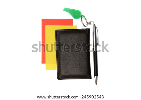 green plastic whistle and red yellow card on white background - stock photo