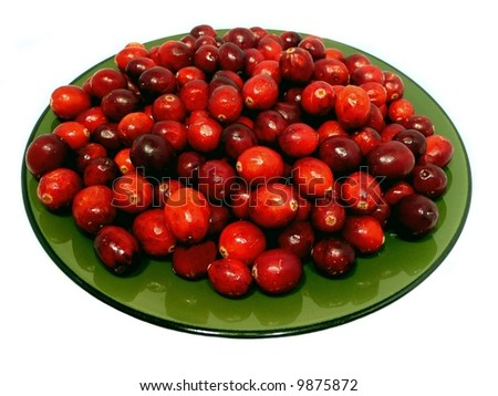 Green plate full of bright red cranberries isolated over a white background - stock photo