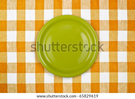 green plate on yellow checked tablecloth - stock photo