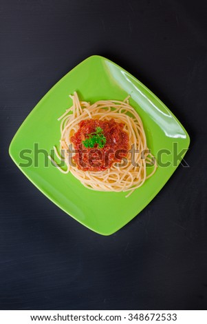 Green plate with spaghetti, sauce on black  background, Top view - stock photo