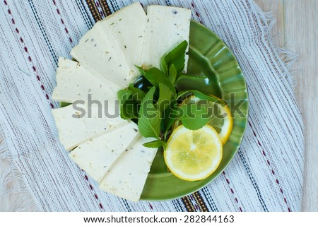 Green plate with tofu, lemon and mint on a linen napkin - stock photo